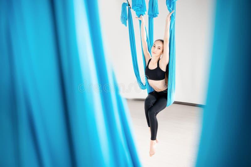 Młoda kobieta wykonuje antigravity powietrznego joga ćwiczenie w białym studiu Pojęcie medytacja zdjęcia royalty free