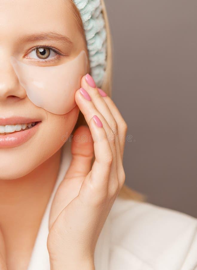 Młoda kobieta z świeżą zdrową skórą i włosami używać łaty i ono uśmiecha się Kosmetologia, piękno i zdrój, obraz stock