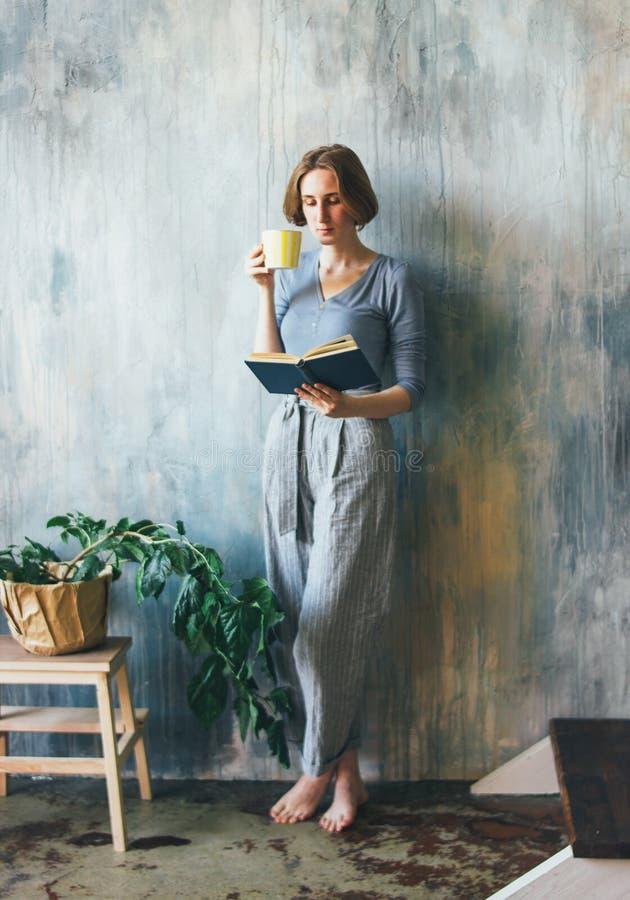 Młoda kobieta z żółtą filiżanki pozycją przeciw ściennej i czytelniczej książce w sztuki pracy studiu, pionowo portret obraz royalty free