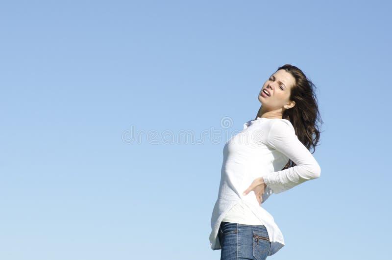 Młoda kobieta z ból pleców zdjęcie royalty free