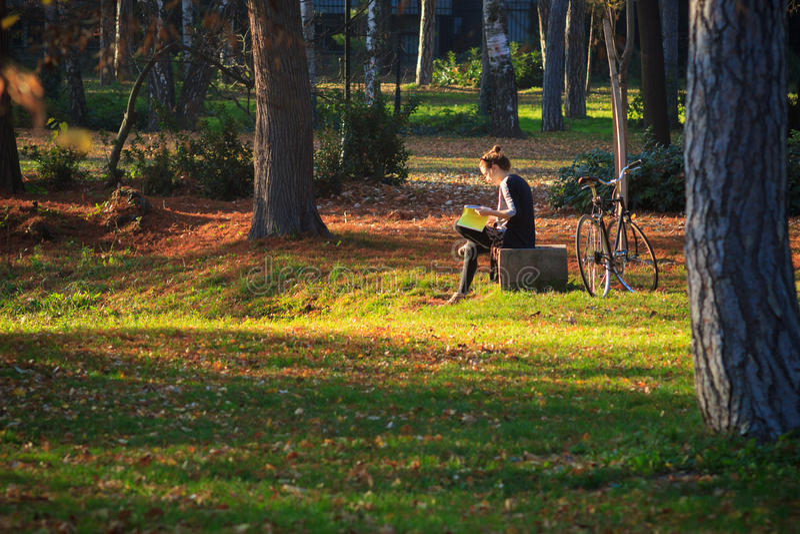 Młoda kobieta z bicyklem, czyta w parku zdjęcie stock