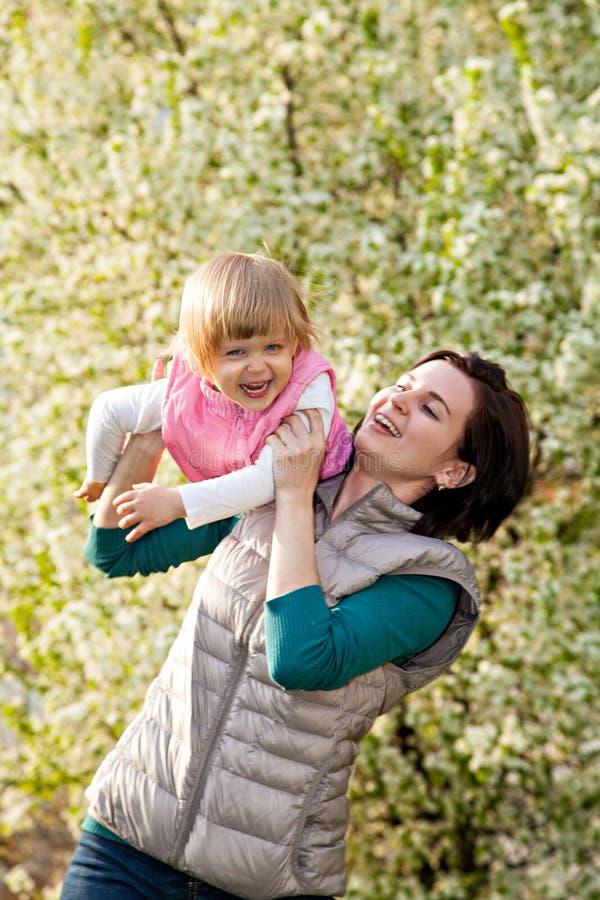 Młoda kobieta z córką bawić się przy parkiem fotografia stock