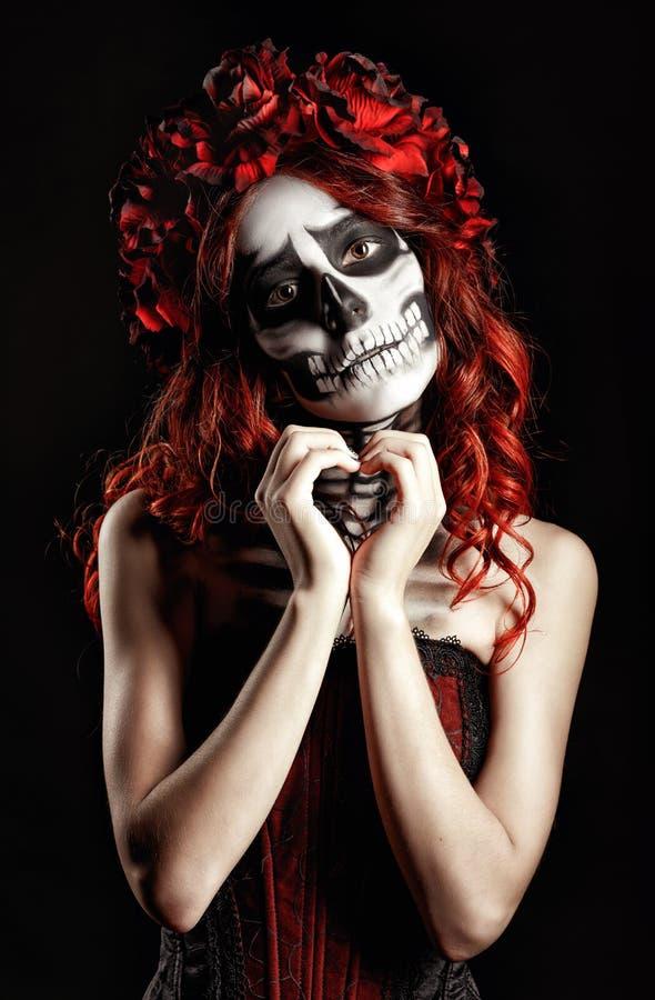 Młoda kobieta z calavera makeup robi sercu podpisywać (cukrowa czaszka) obraz royalty free