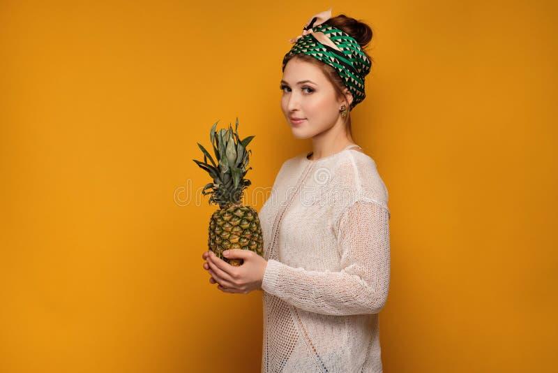 Młoda kobieta z chustką trzyma ananasa, żółty tło obrazy stock