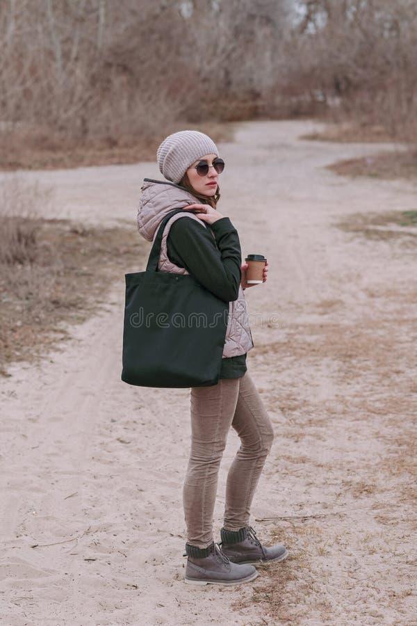 Młoda kobieta z czarną bawełnianą torby i papieru filiżanką w ona ręki Egzamin próbny Up zdjęcie stock