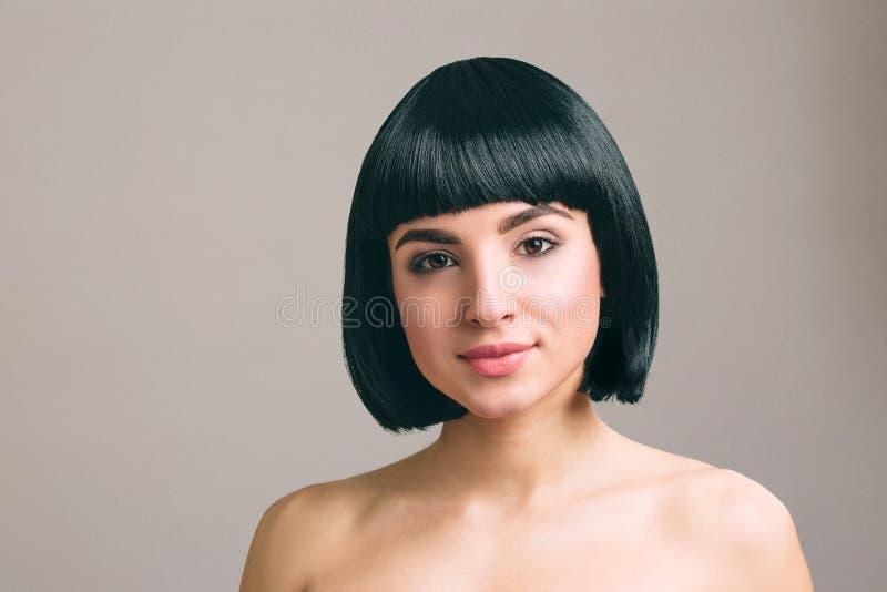 Młoda kobieta z czarni włosy pozuje na kamerze Odizolowywaj?cy na lekkim tle koczka ostrzy?enie Nowożytny modny obrazek zdjęcia stock