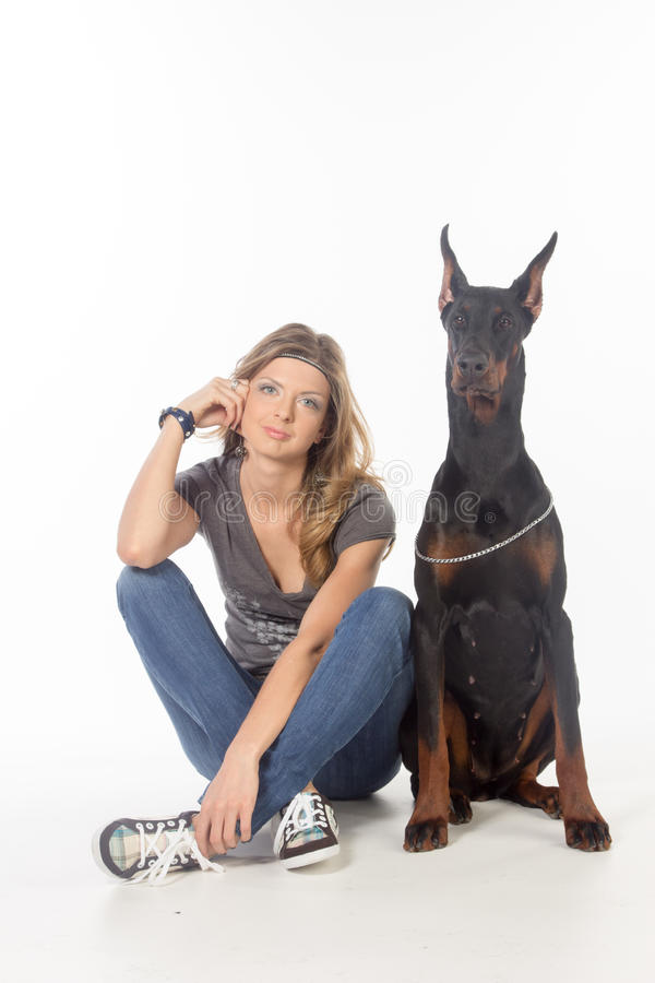 Młoda kobieta z czarnym dobermann psem zdjęcia stock