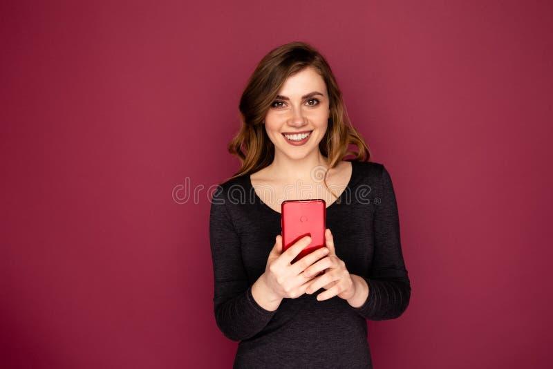Młoda kobieta z czerwoną wiszącą ozdobą odizolowywającą na różowym tle fotografia royalty free