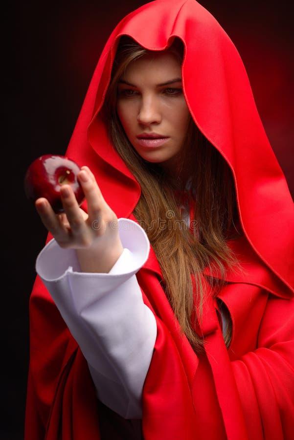 Młoda kobieta z czerwonym peleryny mienia jabłkiem w jej ręce obrazy stock