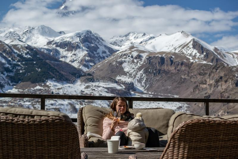 Młoda kobieta z dziecko napoju apperol koktajlem na tarasie hotel z scenicznym widokiem górskim w Kazbegi, Gruzja obraz stock