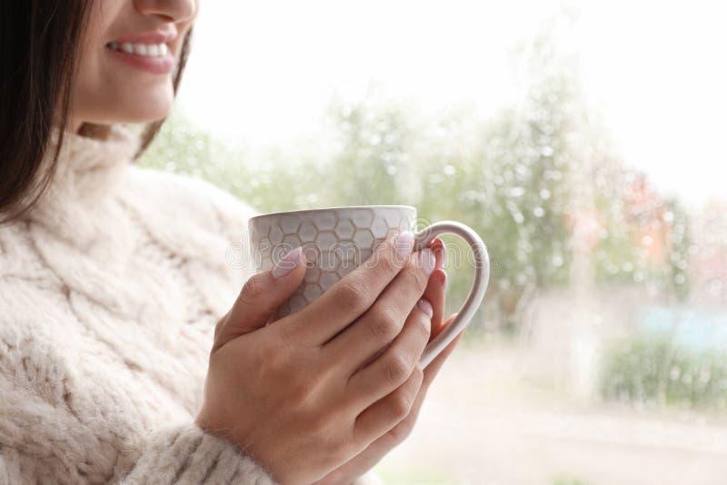 Młoda kobieta z filiżanką herbaciany pobliski okno indoors na deszczowym dniu zdjęcie royalty free