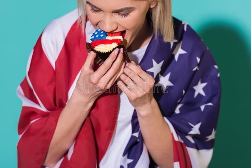 młoda kobieta z flaga amerykańskiej łasowania babeczką na błękitnym tle, odświętność 4th obraz royalty free
