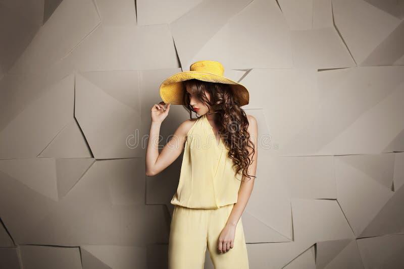 Młoda kobieta z kędzierzawą fryzurą w żółtym kapeluszu i kombinezonie na popielatym graficznym tle obraz royalty free