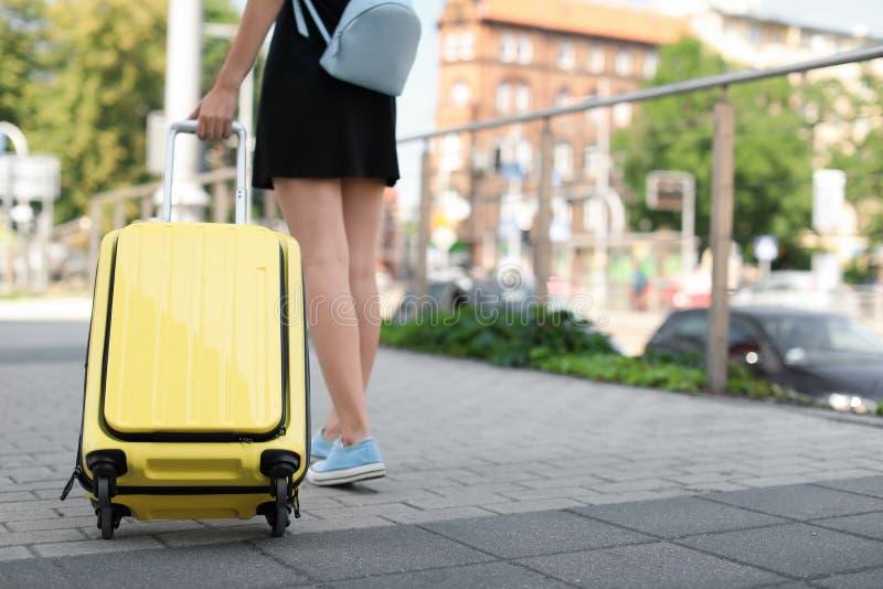 Młoda kobieta z kolorem żółtym niesie na walizce zdjęcia royalty free