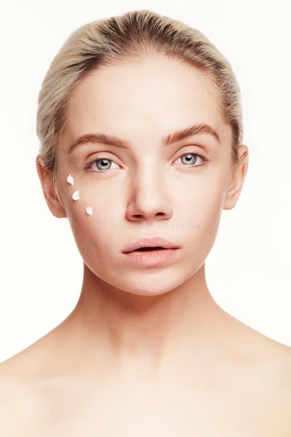 Młoda kobieta z kroplami śmietanka na jej twarzy obrazy stock