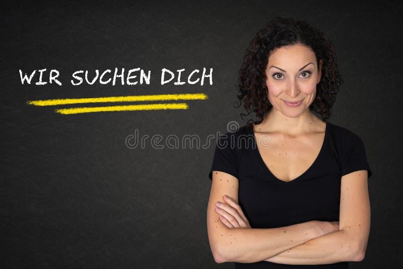 Młoda kobieta z krzyżować rękami i «Wir «suchen dich tekst na blackboard tle Przekład: «szukamy was « royalty ilustracja