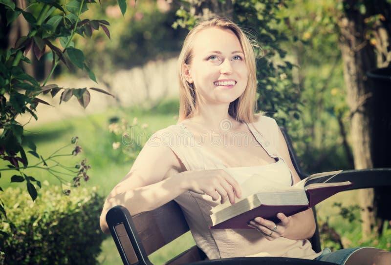 Młoda kobieta z książką w ogródzie zdjęcie stock