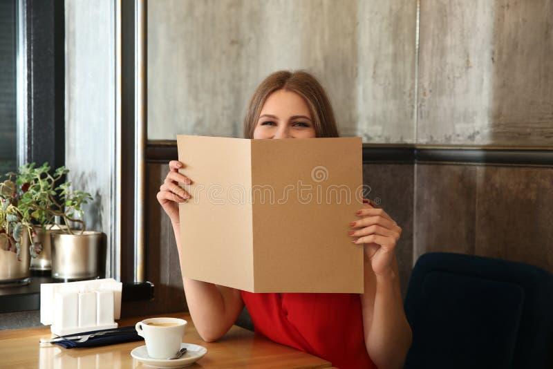 Młoda kobieta z menu obsiadaniem w restauracji zdjęcia royalty free