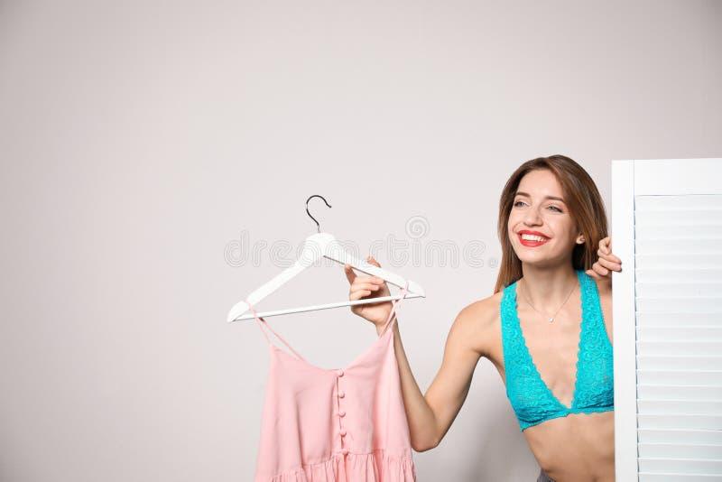 Młoda kobieta z odziewa na wieszaku za falcowanie ekranem przeciw lekkiemu tłu, przestrzeń dla teksta fotografia stock