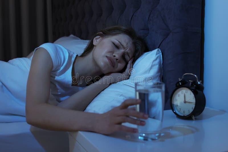 Młoda kobieta z okropną migreną przy nocą bierze szkło obrazy royalty free
