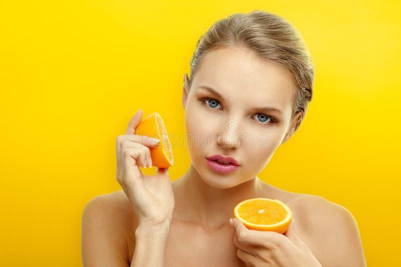 Młoda kobieta z owoc na jaskrawym pomarańczowym tle zdjęcie royalty free