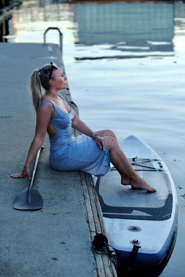 Młoda kobieta z paddle deską i wiosła obsiadaniem na molu w Vancouver Yaletown obraz stock