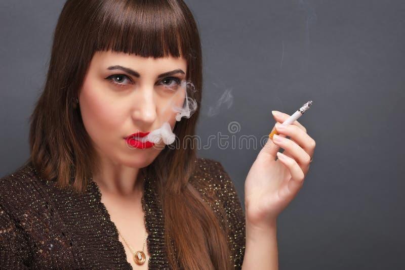 Młoda kobieta z papierosem w jego ręce zdjęcia royalty free