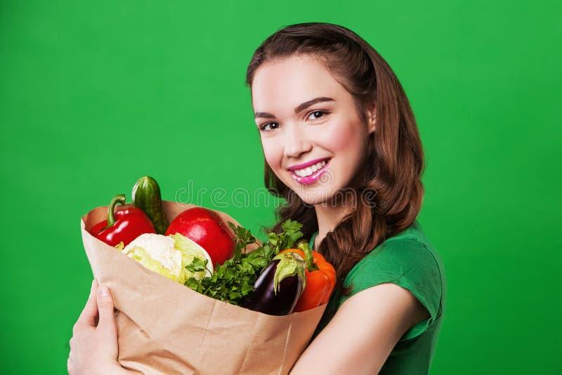 Młoda kobieta z papierową torbą warzywa Na zielonym tle obrazy royalty free