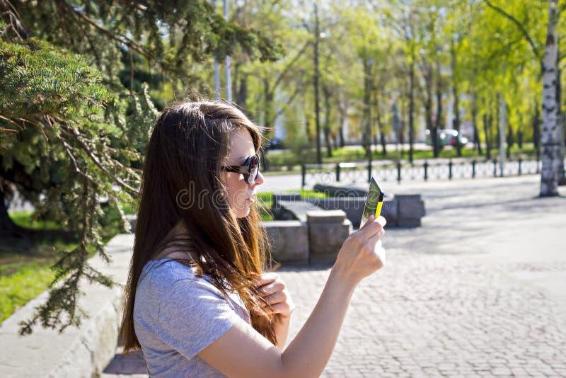 Młoda kobieta z pastylką w miasto parku zdjęcia stock