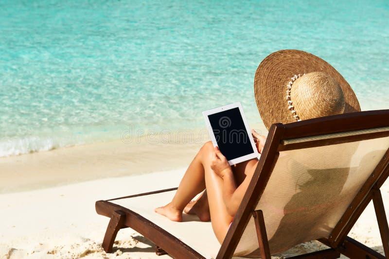Młoda kobieta z pastylka komputerem osobistym przy plażą zdjęcie stock