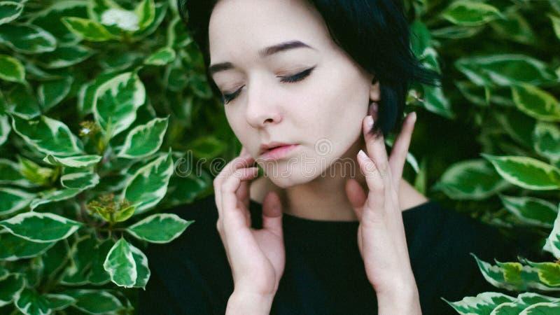 Młoda kobieta z pięknymi ciekami ubierał w czerni sukni, przeciw tłu miastowy krajobrazu krzak obraz royalty free