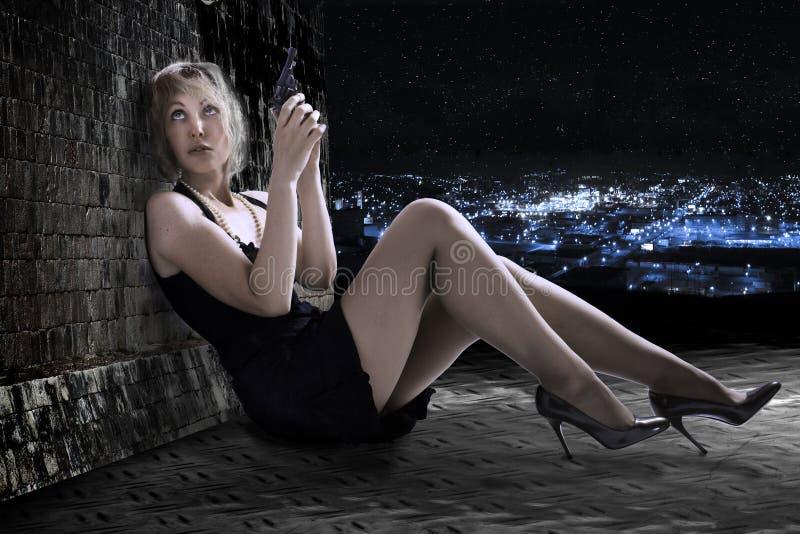Młoda kobieta z pistoletem na dachu. zdjęcie royalty free
