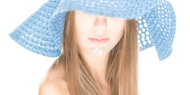 Młoda kobieta z połówka chującą twarzą pod błękitnym kapeluszem. zdjęcia stock
