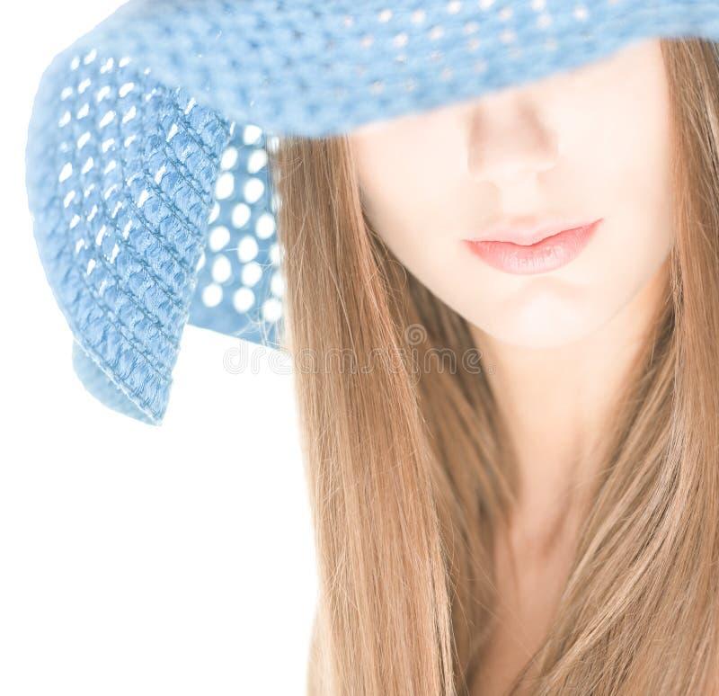 Młoda kobieta z połówka chującą twarzą pod błękitnym kapeluszem. obrazy royalty free