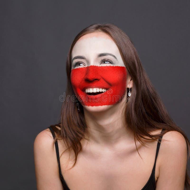 Młoda kobieta z Polska flaga malującą na jej twarzy zdjęcie stock