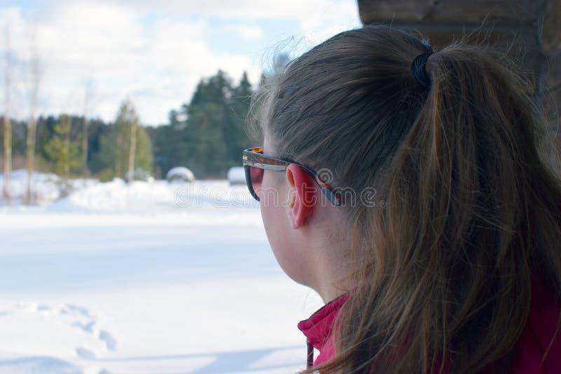 Młoda kobieta z ponytail dopatrywania zimy krajobrazem na jej swój myślach fotografia stock