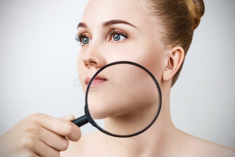 Młoda kobieta z powiększać - szklana czek skóra zdjęcia royalty free
