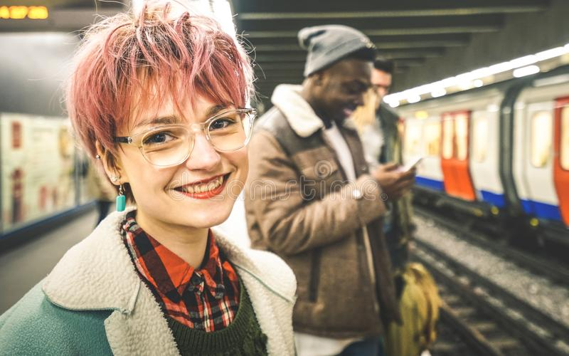 Młoda kobieta z różowym włosy i grupą multiracial modnisiów przyjaciele przy stacją metru fotografia stock
