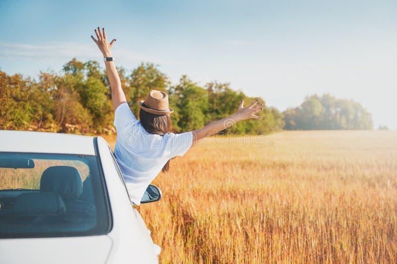 Młoda kobieta z rękami podnosić w białym samochodzie na polu zdjęcie royalty free