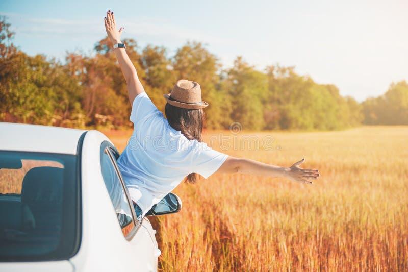 Młoda kobieta z rękami podnosić w białym samochodzie na polu zdjęcie stock