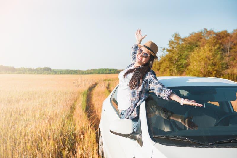 Młoda kobieta z rękami podnosić w białym samochodzie na polu obraz stock