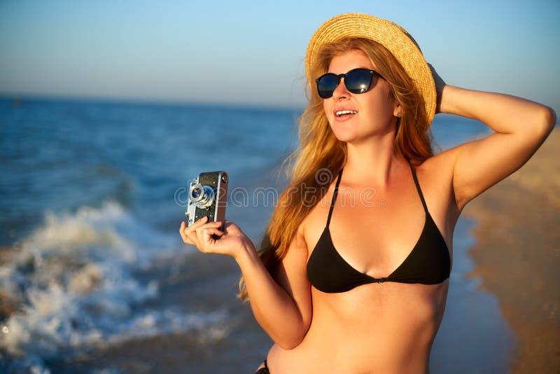 Młoda kobieta z rocznik retro ekranową kamerą cieszy się tropikalną plażę na wakacje Żeńskiego ciała pozytywu fotograf zdjęcie royalty free