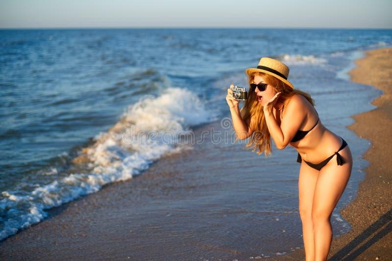 Młoda kobieta z rocznik retro ekranową kamerą cieszy się tropikalną plażę na wakacje Żeńskiego ciała pozytywu fotograf obrazy royalty free