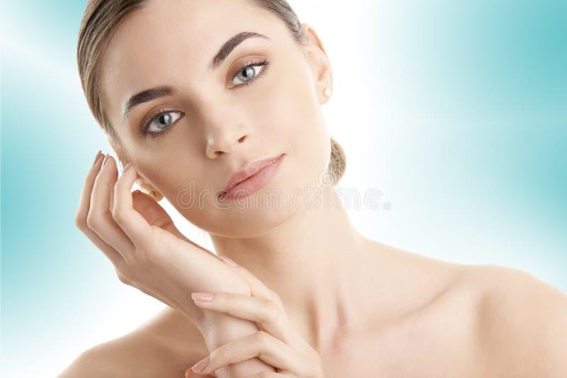 Młoda kobieta z rozjarzoną skórą pozuje przy odosobnionym bławym tłem fotografia royalty free