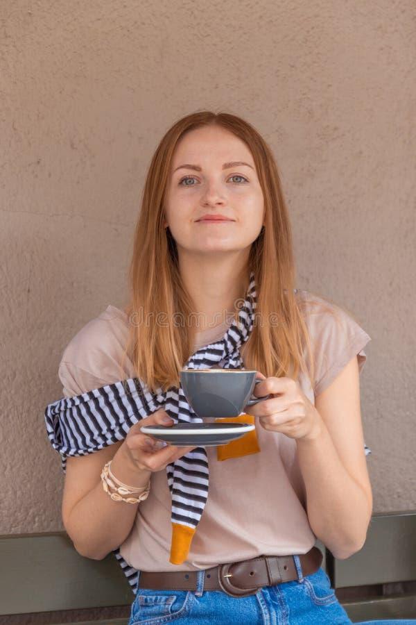 Młoda kobieta z słodkim uśmiechem z filiżanką kawy, relaksująca się w kawiarni obraz stock
