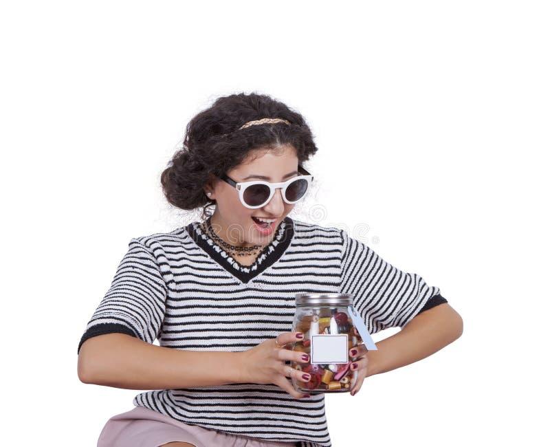 Młoda kobieta z słojem cukierki obraz stock