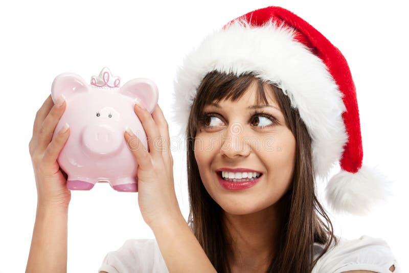 Młoda kobieta z Santa nakrętki mienia prosiątka bankiem zdjęcia royalty free