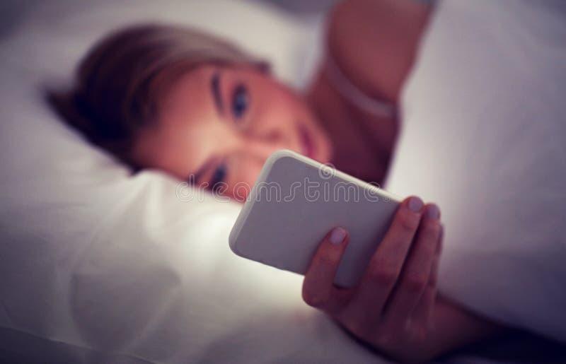 Młoda kobieta z smartphone w łóżko sypialni w domu obraz royalty free