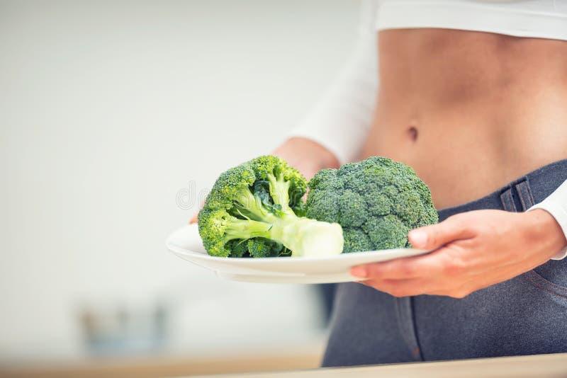 Młoda kobieta z sport postacią w kuchennym mieniu w ona ręki i talerz brokuły fotografia stock