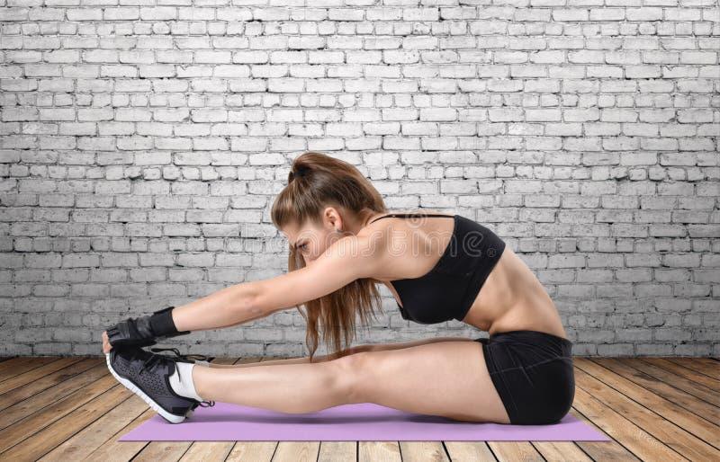 Młoda kobieta z sportowym ciałem robi rozciąganie treningowi w szkolenie sukni, ostrość na rękach obrazy stock